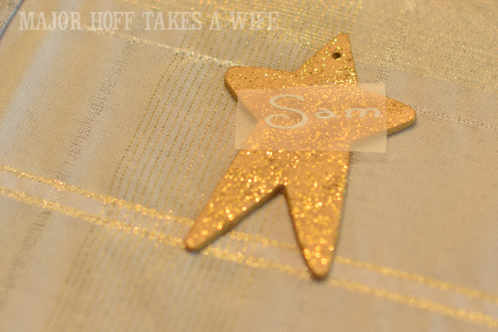 Transfering name onto ornament using transfer tape. Looking for homemade Christmas gifts? Look no further than these homemade Christmas ornaments. Use them as tree decorations, to grace your holiday table, or for fun tags to gifts! The ideas and endless and your friends and family will love these glittery stars personalized just for them!