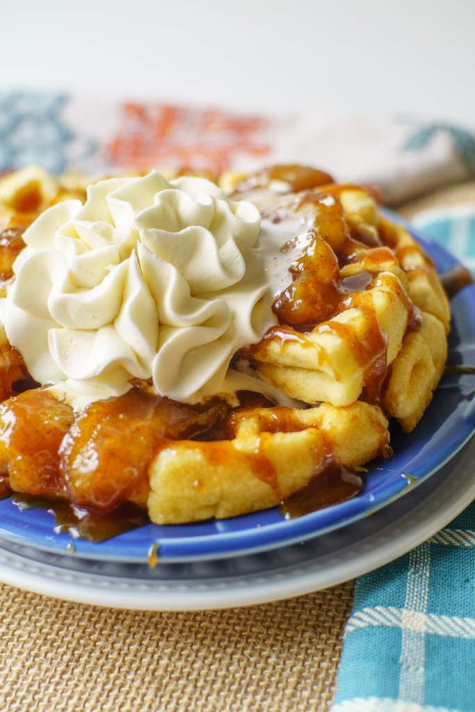 waffles with caramelized bananas and a whipped cream flower on top
