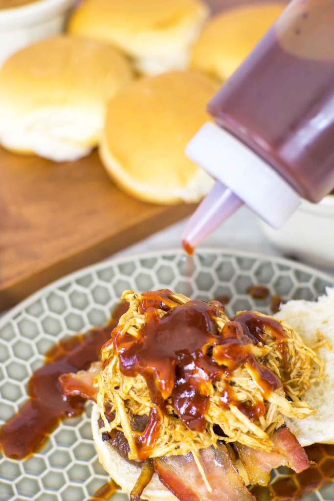 adding maple barbecue sauce to sliders made with pulled chicken breasts