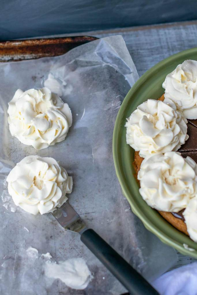 sturdy whipped cream frosting is used to pipe flower shapes to decorate a pie or cake