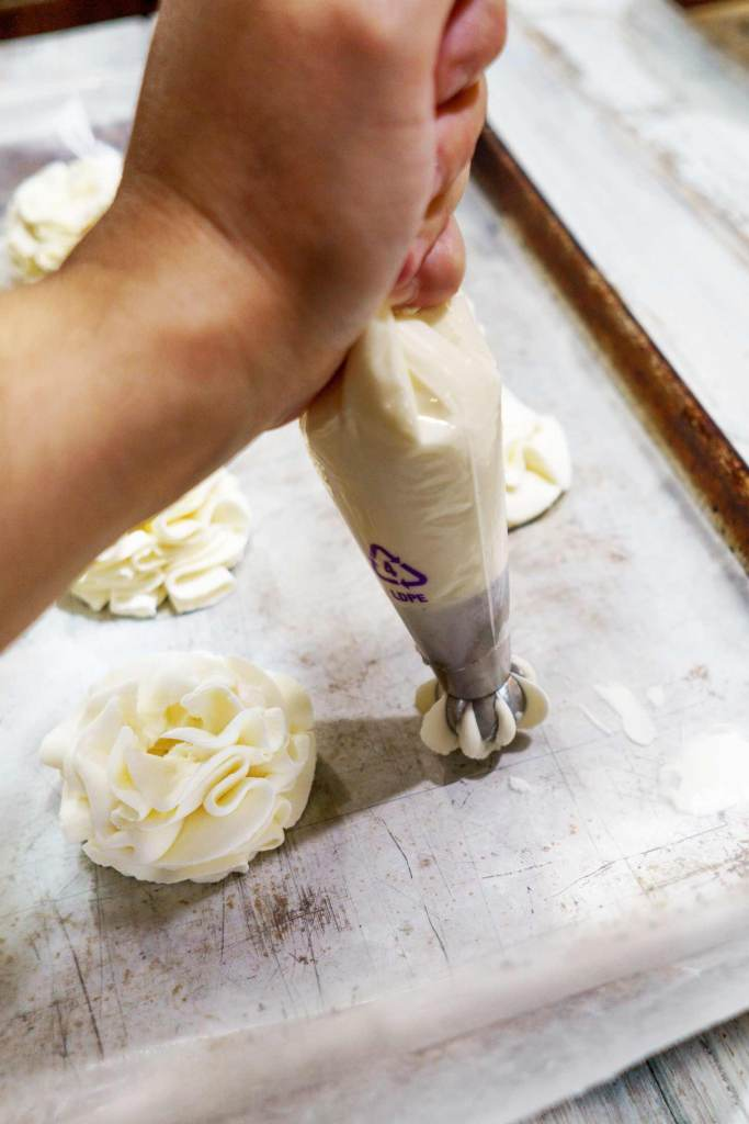 a russian piping tip is used to pipe stabilized whip cream frosting directly onto wax paper from a disposable piping bag
