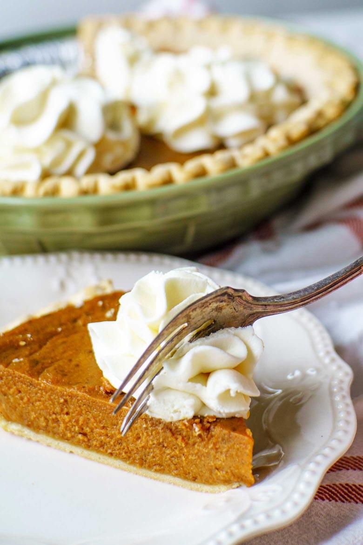 A fork full of molasses pumpkin pie on a dinner table set for thanksgiving