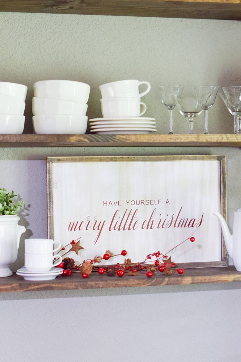 a rustic farmhouse sign on wooden shelves for a Christmas holiday display with white dishes
