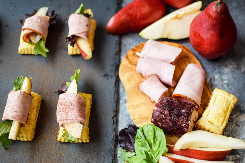 serving goat cheese and meat roll ups on puff pastry on a slate serving board makes for an appealing way to serve appetizers