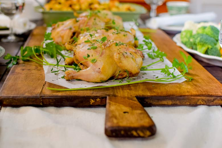 roasted cornish hens with fresh herbs on a thanksgiving table