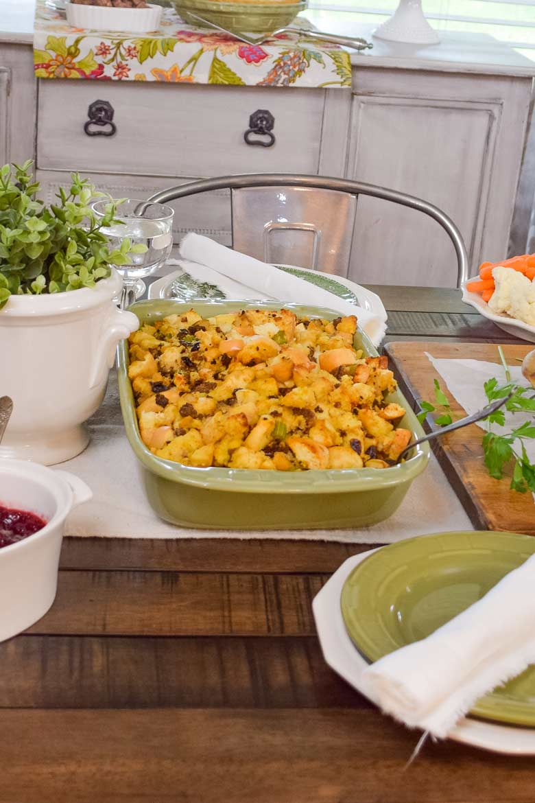 Herb stuffing baked in a pretty green dish to go along side other Thanksgiving favorites like cranberry sauce