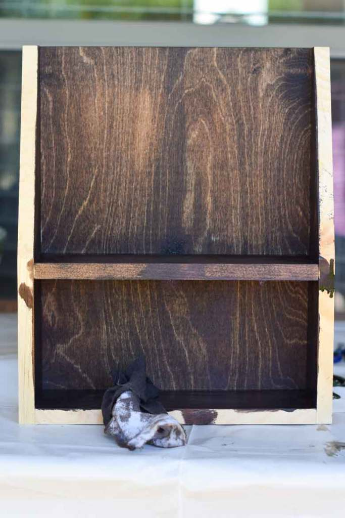 Staining an unfinished pine shelf is easy with an old t-shirt, minwax stain, and a disposable glove. Simply start on the inside and work your way out.