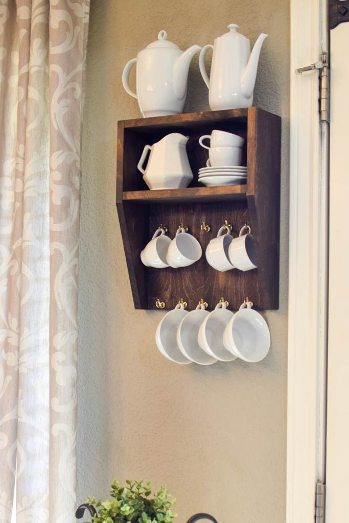 White dishes and cups hanging on a small dining room shelf for cup and mug storage