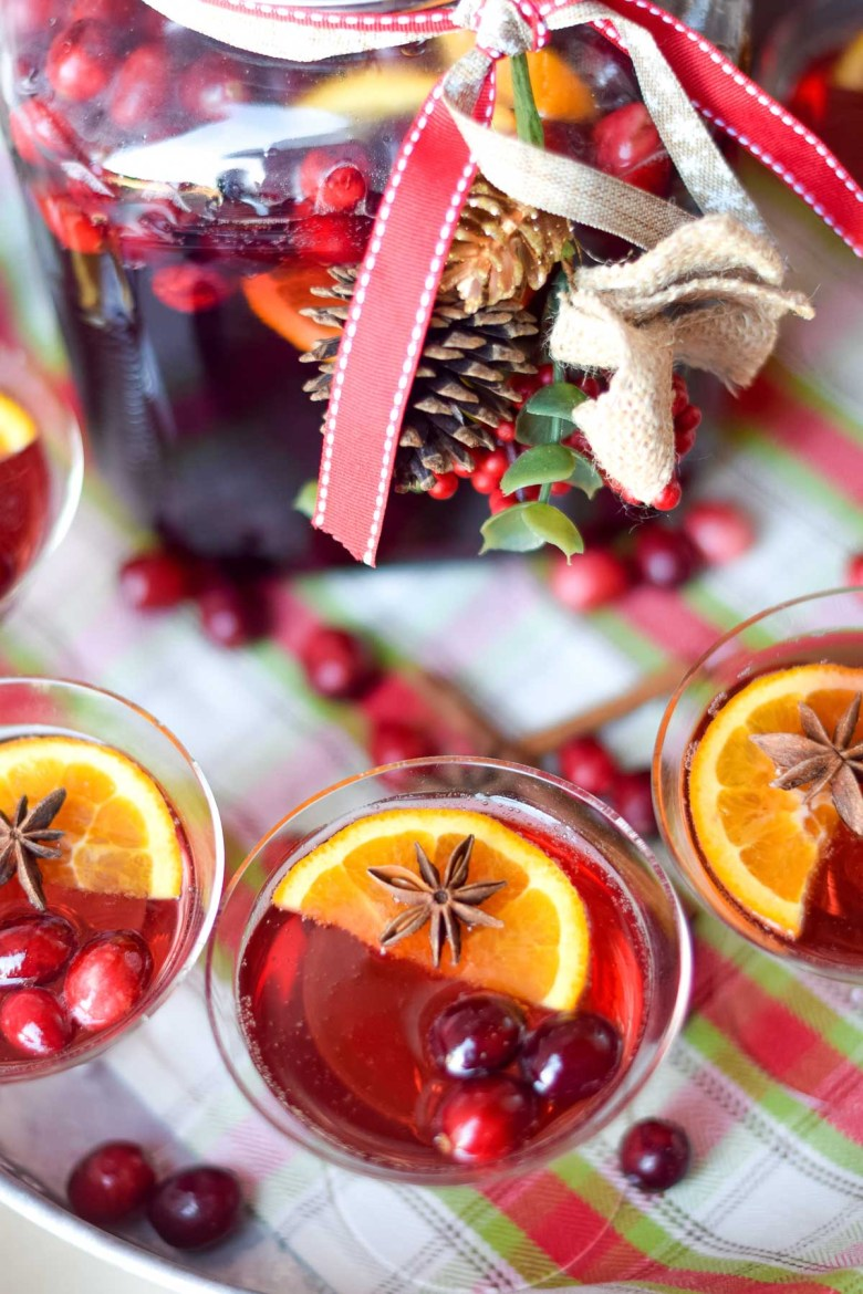 Cranberry ginger ale punch in champagne glasses with oranges, cranberries and star anise