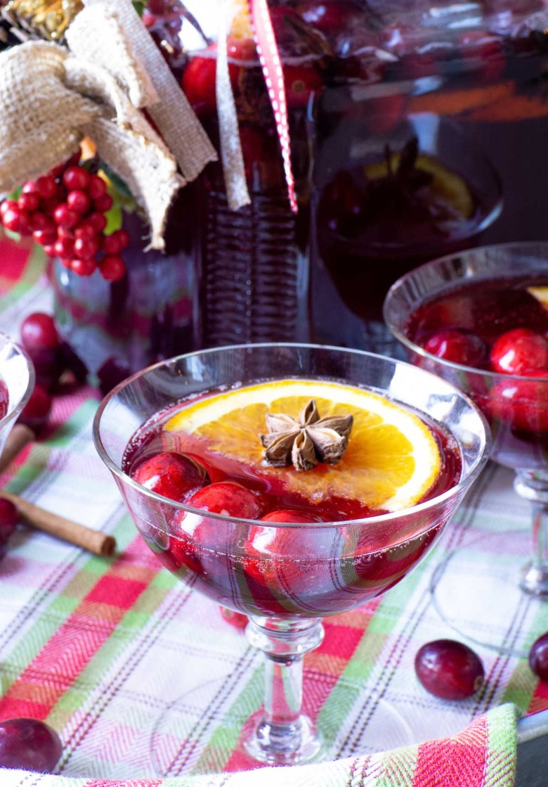 A star anise spice sits atop an orange slice in a cranberry holiday beverage served in a champagne glass