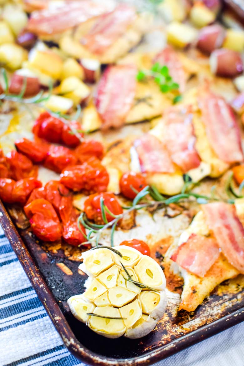 baked garlic, tomatoes and chicken with bacon on a single sheet pan