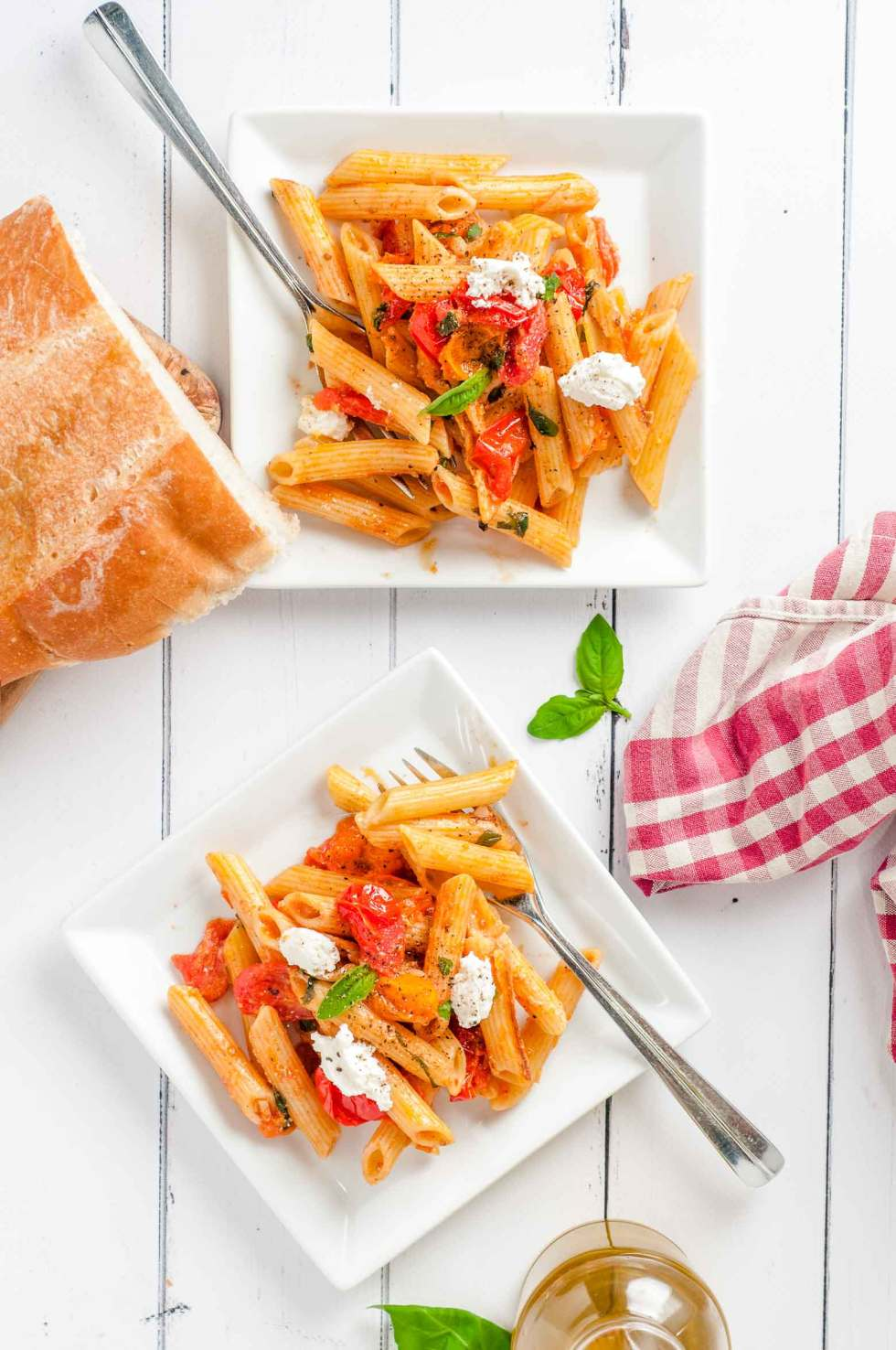 bread, a red checked napkin and 2 plates of rigatoni noodles coated in a tomato basil sauce