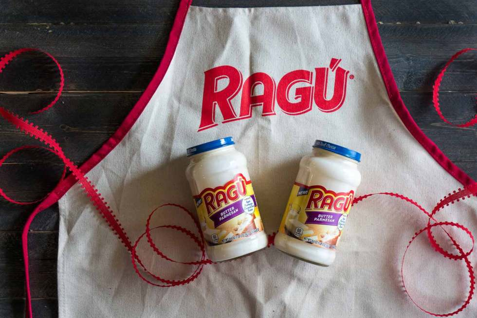 RAGÚ® butter parmesan sauce jars on an apron