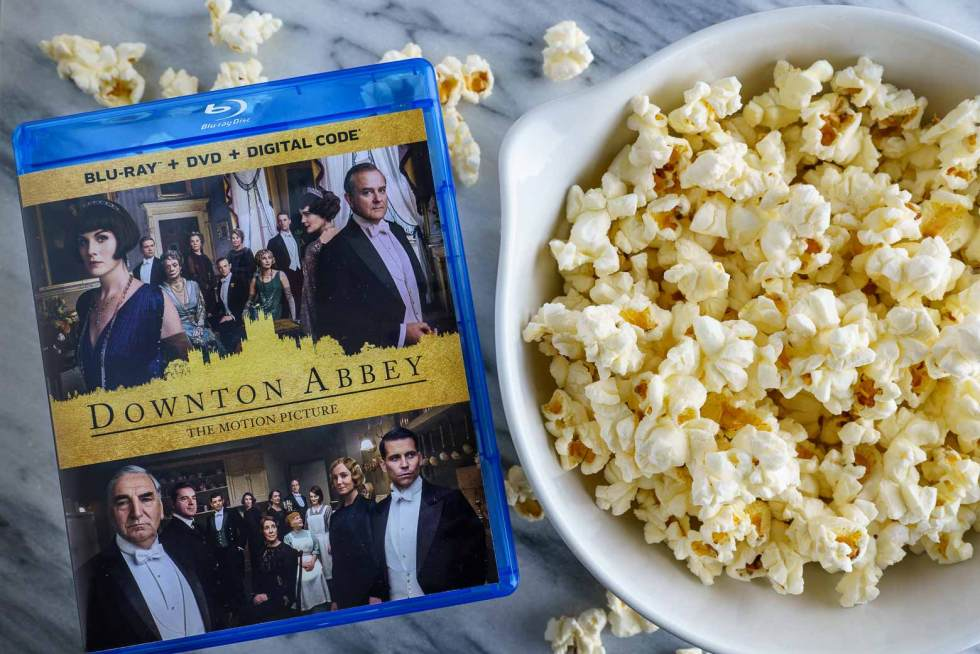 Downton Abbey Film DVD next to a bowl of popcorn