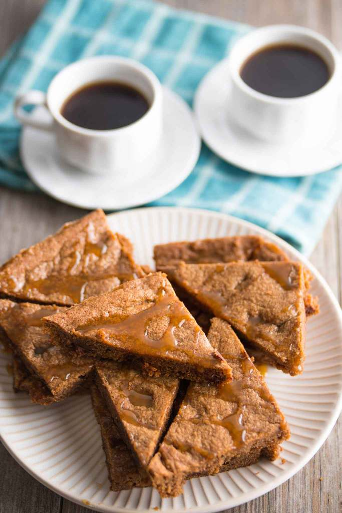 crispy chocolate chip cookie bars with caramel bits on a white plate with two cups of espresso