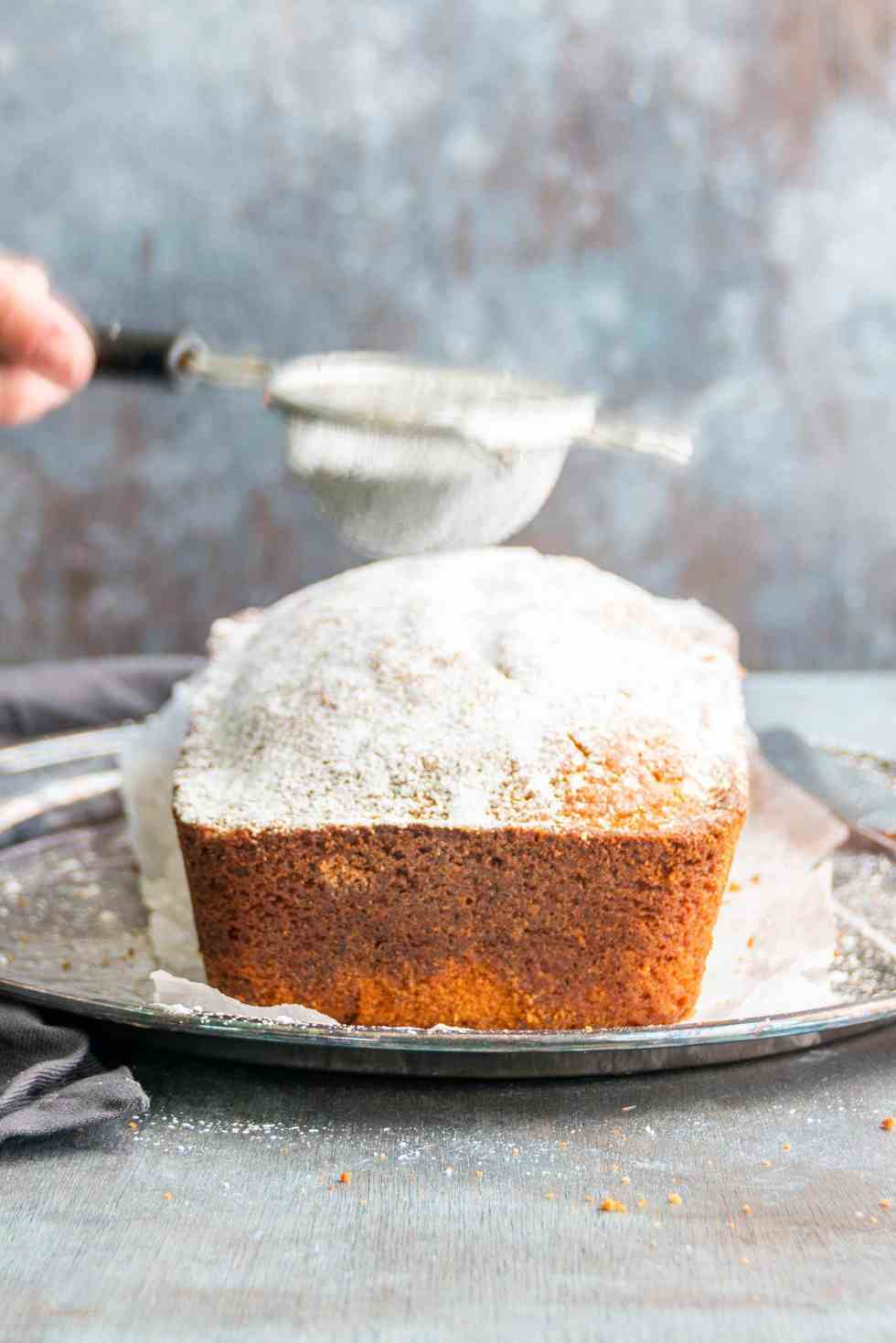 dusting powdered sugar on an autumn spice loaf cake