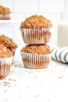 two stacked oatmeal banana muffins with white liners next to a towel
