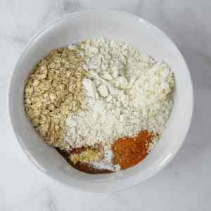 Dry ingredients in a white bowl including coconut and oatmeal
