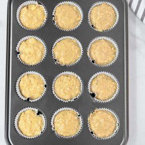 muffin batter in a gray muffin tin