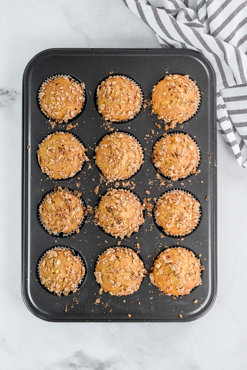 muffins in a grey tin out of the oven next to a towel
