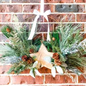 large metal wreath full of Christmas greenery