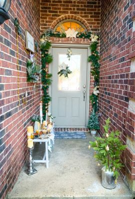 A bench on front porch with a wall of wreaths and a garland covered from door.