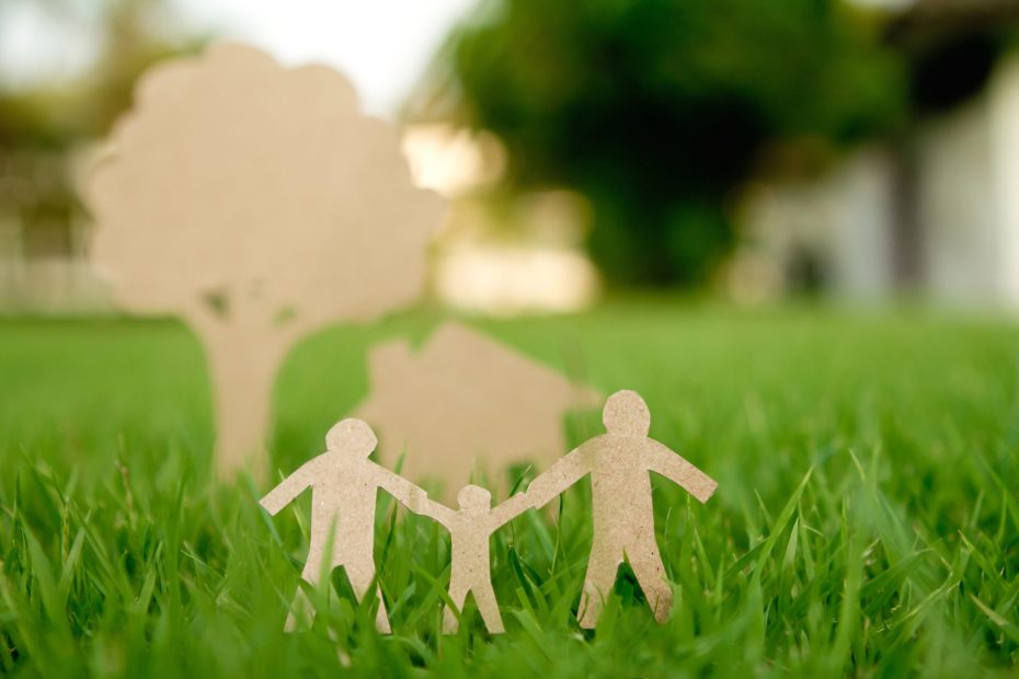 Cardboard family figures cutout sitting on grass