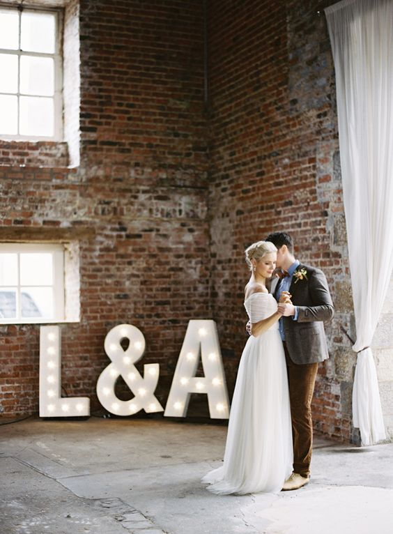 Bride & groom together beside illuminated monograms