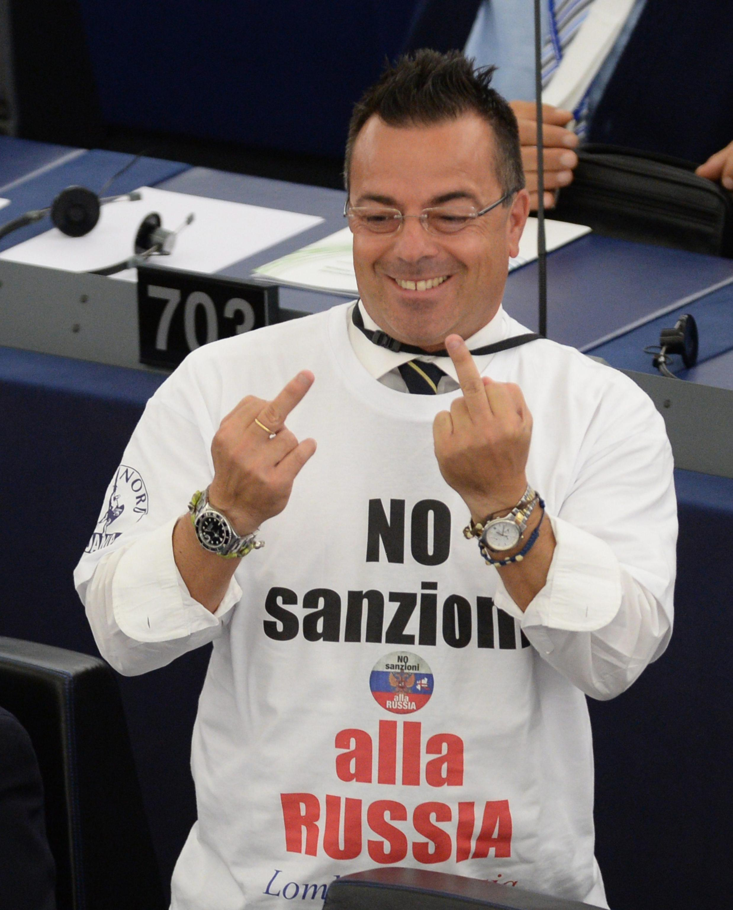 epa04402541 Italian member of the European Parliament (MEP) Gianluca Buonanno, of the Italian Lega Nord, wears a protest t-shirt with the slogan 'No Sanzioni alla Russia' (No Sanctions on Russia) during the plenary session at the European Parliament in Strasbourg, France, 16 September 2014. The parliaments of Ukraine and the European Union were set 16 September to ratify a landmark political and free trade deal, but some lawmakers expressed displeasure over a delay in the agreement. The political and trade deal ratified by parliaments in Ukraine and the European Union were the first step towards membership in the bloc, Ukrainian President Petro Poroshenko said. EPA/PATRICK SEEGER