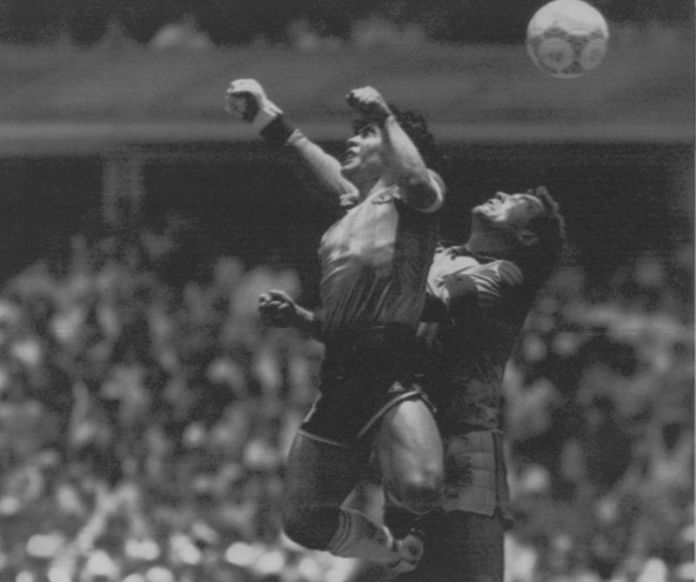 """** FILE ** Argentina's Diego Maradona, left, beats England goalkeeper Peter Shilton to a high ball and score his first of two goals in a World Cup quarterfinal in Mexico City, in this June 22, 1986 photo. Argentina won 2-1. Maradona acknowledged that he struck the ball with his hand in the famous """"Hand of God"""" goal against England in the 1986 World Cup quarterfinals. Speaking on his local television talk show Monday night, Aug. 22, 2005, Maradona called one of soccer's most controversial goals """"something that just came out of me. It was a bit of mischief."""" (AP Photo/El Grafico, Buenos Aires)"""