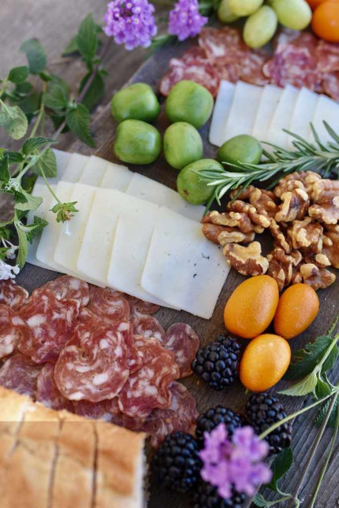 Gorgeous cheese plate with fresh fruit, flowers, cheese, bread, and sausage.