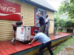 Putting rollers under the Coca Cola cooler to move it across the porch.