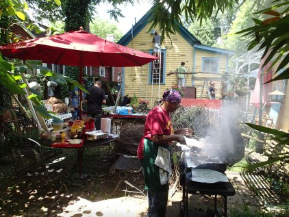 Day 1: Bertha cooks while volunteers scrape.