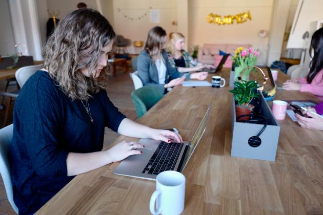 four women at a table with lap top