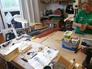 Sue refers to the model desk. In the foreground, plastic boxes to hold the wiring