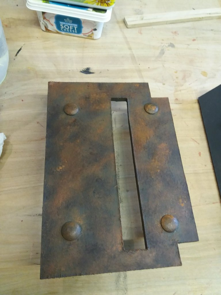 letter painted to resemble rusty metal with rivets