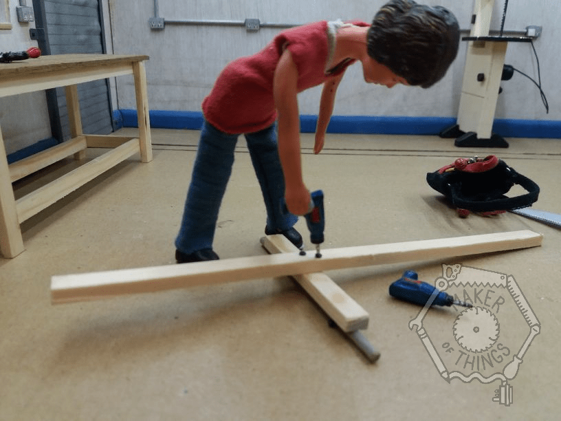 Harriet has the timber placed over the axle on the floor, and is screwing them together.