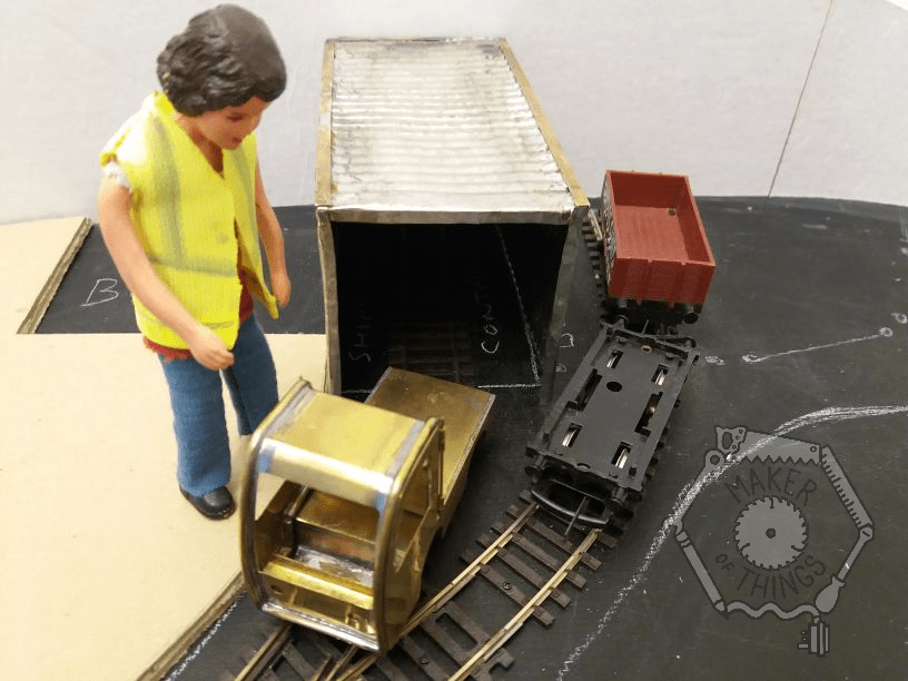 Harriet is standing next to a brass locomotive in front of the miniature shipping container, and there are some wagons nearby.