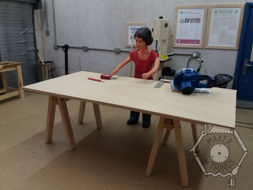 Harriet is in her workshop. There is a sheet of 8x4 plywood board resting on two saw horses. Harriet has her pencil, tape measure, try square, and circular saw on the board. Harriet is deciding where to start with the design.