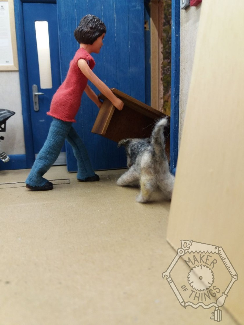 Harriet is pulling a small heavy brown bench through the workshop door. Monty the dog is trying to get underneath it.
