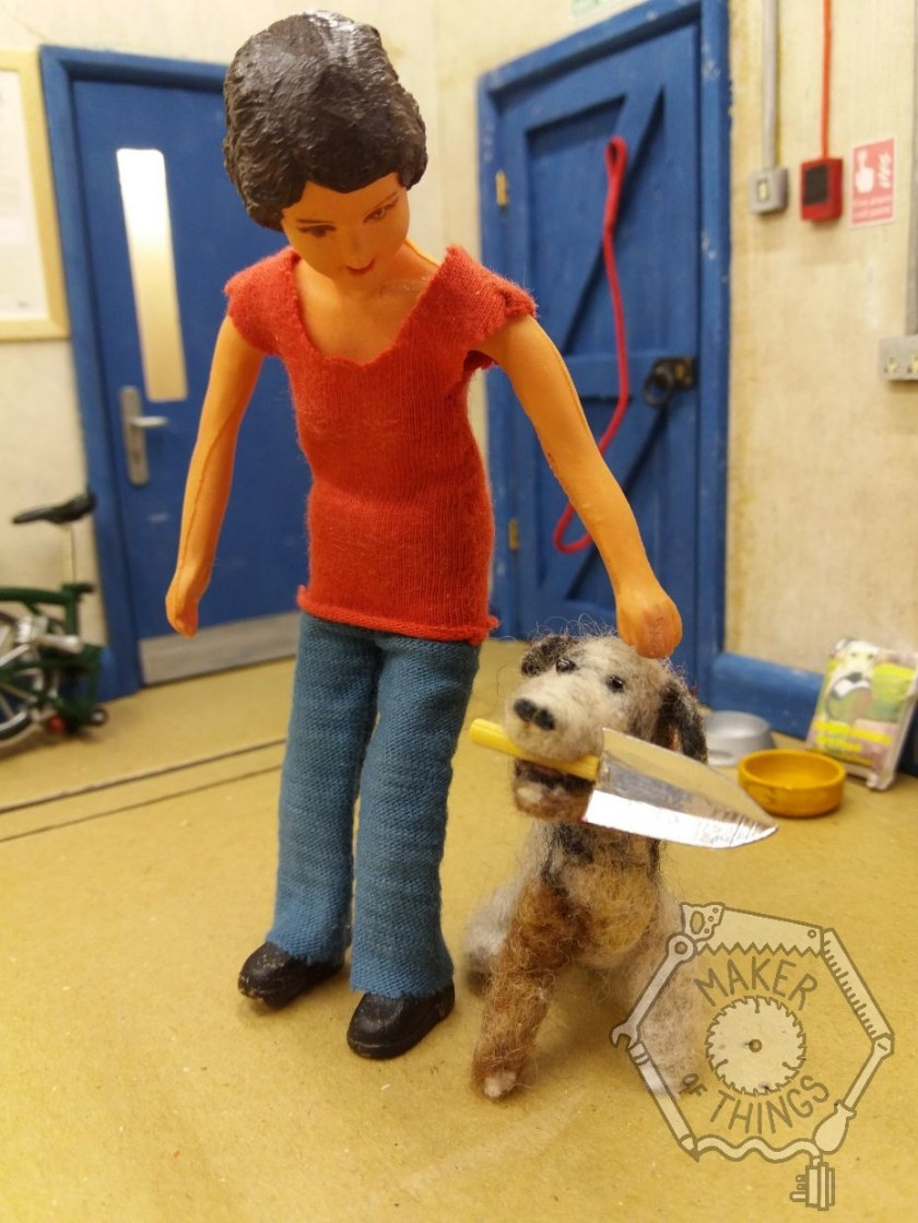 Harriet is standing in her workshop with her dog, Monty. Monty is a scruffy grey and black dog with a brown right front leg, and has a gardening trowel in his mouth. He is sitting next to Harriet. In the background is two blue doors and Monty's red lead is hanging on the back of the door. There are dog bowls and dog food next to the door.