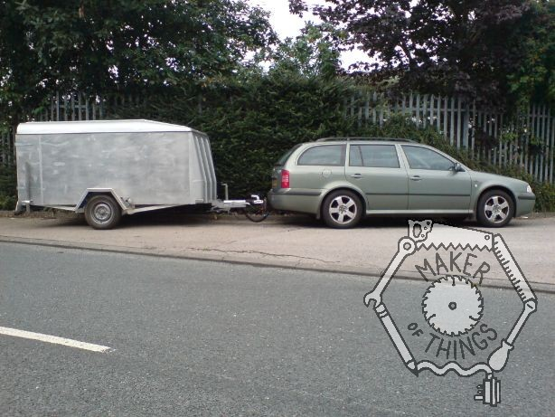 A green Skoda Octavia Estate with a big silver box trailer in tow. Parked on an access driveway with a tall hedge background.