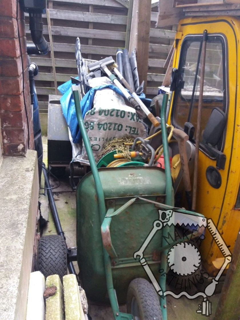 A compact electric tractor next to a brick wall covered with a builder's bulk bag and a gree wheel barrow. The yellow cab of Beryl The EV is next to the tractor.