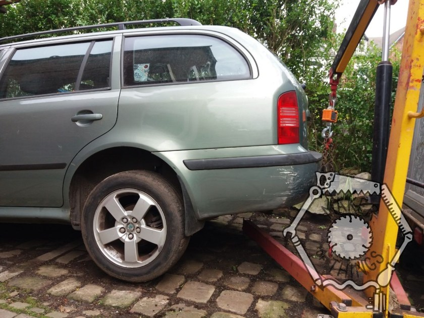 The back end of the green Skoda estate car being lifted into the air with an engine crane attached to the tow hitch with a crane scale to weigh the car.