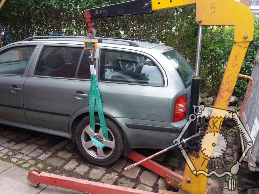 The near side rear wheel of the green Skoda estate car being lifted with an engine crane and crane scales with a strap through the wheel spokes.