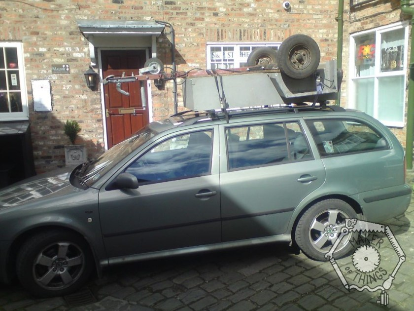 My green Skoda Octavia Estate with a small trailer upside down on the roof rack.