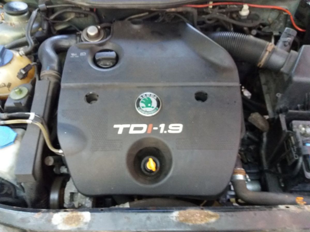 An under bonnet view of the Skoda Octavia 1.9 TDi engine showing the plastic engine cover, and ancillaries.