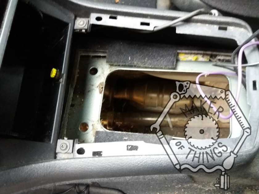A view of the centre console inside the car showing a large hole where the gear stick mechanism used to be.