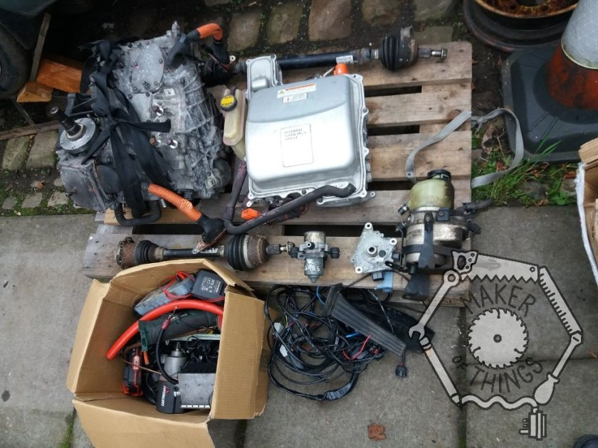 The pallet with the boxes removed and part emptied. there is an electric drive gearbox and controller from a Toyota Prius, an electric power steering pump, an electric vacuum pump, an electric throttle pedal, a pile of wiring, other bits I don't recognise, and a box of random 'stuff'.