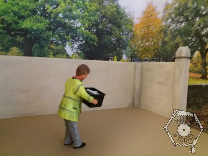 The recycling man has picked up the recycling box and is heading across the courtyard.